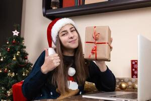 Girl in santa claus hat using laptop for video call to friends and parents photo