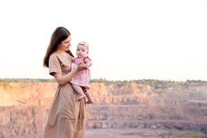 Happy young mother holds her young baby daughter in her arms outdoors photo