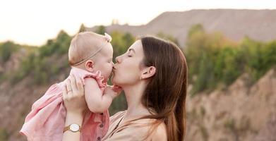 mamá sostiene a un niño en sus brazos y lo besa suavemente en la mejilla al aire libre foto