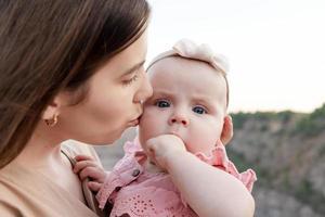 mamá sostiene a un niño en sus brazos foto