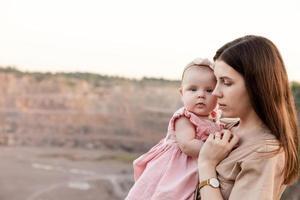 mamá sostiene a su hija en sus brazos foto