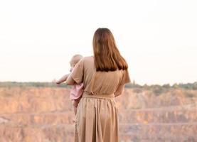 una joven madre está de pie mirando la cantera o las montañas y sostiene a un niño en sus brazos foto