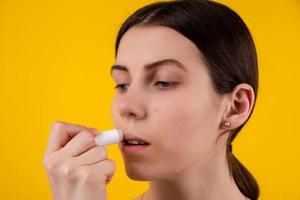 Attractive young woman using hygienic lipstick on yellow background photo