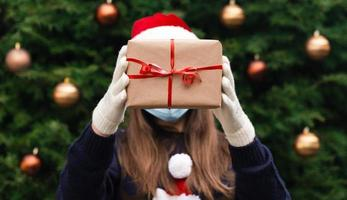 Faceless portrait of a woman holding gift box with red ribbon on a Christmas background photo