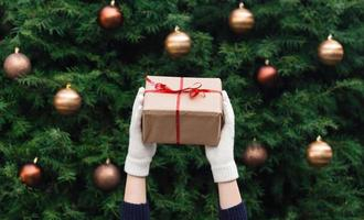 Female hands in white knitted gloves hold a Christmas gift wrapped in craft paper photo