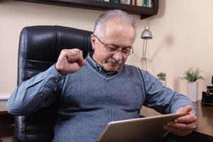 Senior man reading news on digital tablet photo