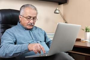 Senior man learns to use computer photo