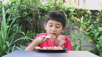 muchacho asiático en camisa roja felizmente comiendo una pizza video