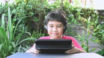 Asian boy wearing wireless headphones and smiling happily while playing games on the tablet video