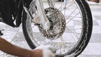 Close-up of a man's hand washing a motorbike front wheels with sponges and bubbles video