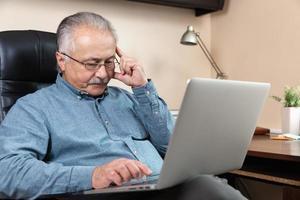 Pensive senior businessman works at home photo