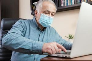 Senior man in face mask working or communicating on laptop at home photo