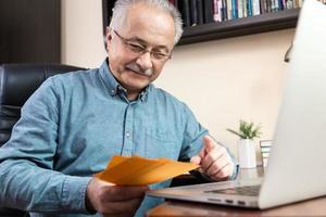 Hombre senior en mascarilla trabajando o comunicándose en un portátil en casa foto