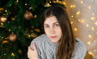 Young beautiful woman in gray knitted dress near Christmas tree photo