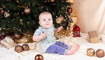 un bebé en jeans se sienta cerca de un árbol de navidad y juega con una guirnalda en la que está enredado foto