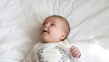 un retrato de primer plano de una niña que yace en la cama y sonríe foto