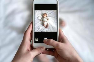 Por encima de un alto ángulo de disparo de mamá feliz tomando fotos de su bebé o niña