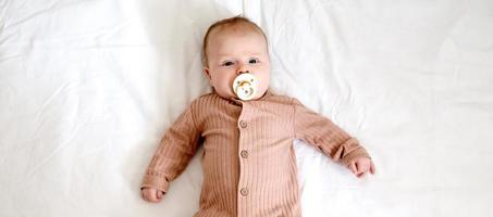 Portrait of a newborn baby girl who lies on a bed with a nipple soother photo