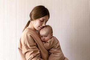 Alegre hermosa joven sosteniendo a una niña en sus manos foto