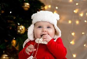 niño de navidad sonríe y sostiene una guirnalda con corazones foto