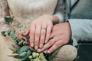 Manos con anillos de la novia y el novio están acostados en el primer ramo de flores foto
