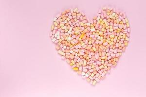Top view of the multicolored marshmallows which lies in the shape of a heart on a monochrome pink background photo