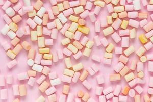 Vista superior de malvaviscos multicolores sobre un fondo rosa monocromo foto