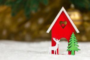 Navidad casa de juguete de madera ciervos y árboles sobre una manta blanca imitando la nieve foto