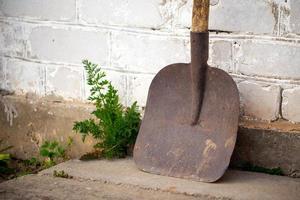 Pala vieja y sucia utilizada en la construcción o la agricultura apoyado en la pared blanca de ladrillo foto