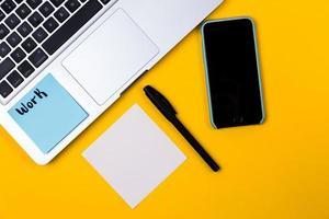 Escritorio de oficina en casa con espacio de trabajo portátil y adhesivo de papel sobre fondo amarillo foto