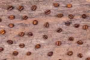 Granos de café aromáticos en la mesa de madera blanca foto