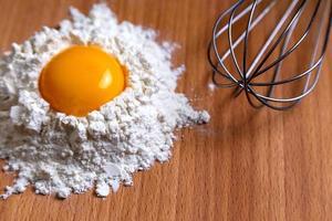 Ingredientes para cocinar y utensilios de cocina en la mesa de madera foto