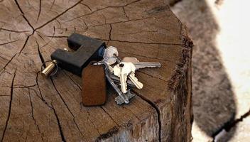 Un manojo de llaves y un candado se encuentran sobre un fondo de madera foto