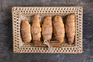 Croissants lie in a wicker basket with cinnamon photo