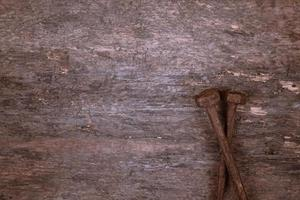 Two old rusty nails rest on a wooden background photo