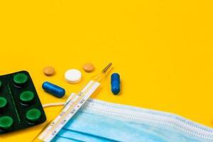 Máscara médica protectora sobre fondo amarillo rodeado de pastillas de colores foto
