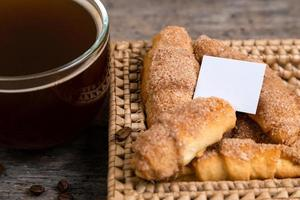 Croissants lie in a wicker basket with tea cup photo