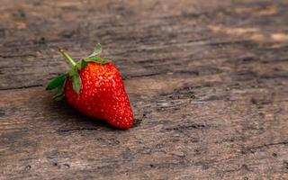 One strawberry on wooden background photo