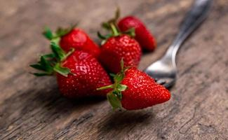 Fresh strawberries and one berry on fork still life on dark wooden background photo