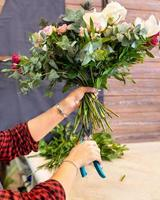 Mujer floristería haciendo ramo de flores en la tienda foto