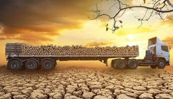 Loaded timber trucks arriving and parked on the cracked soil in arid areas of a landscape at sunset and cloud background photo