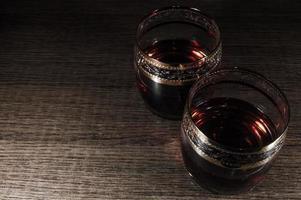 Glass of dark red whiskey brandy or bourbon photo