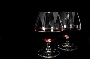 Glass of dark red brandy whiskey or bourbon photo
