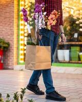 Man walking with shopping bag inside Moth orchids Phalaenopsis photo