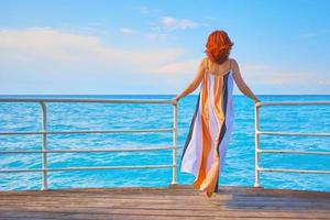 Woman on pier with sea background photo