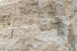 Muro de arena de arena clara con pequeños guijarros foto