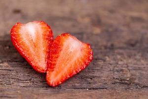 Cortar la fresa roja madura sobre un fondo de madera foto
