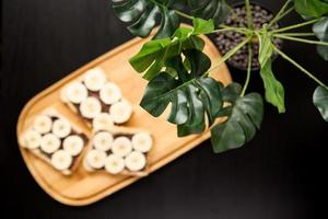 Three banana white bread toasts spread with chocolate butter on a chopping board with leaves on a dark background photo