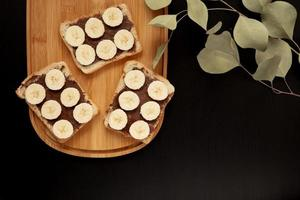 Three banana white bread toasts smeared with chocolate butter on a cutting board against a dark background photo