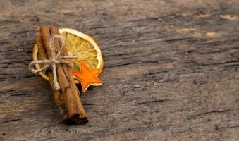 un montón de ramas de canela y naranja seca foto